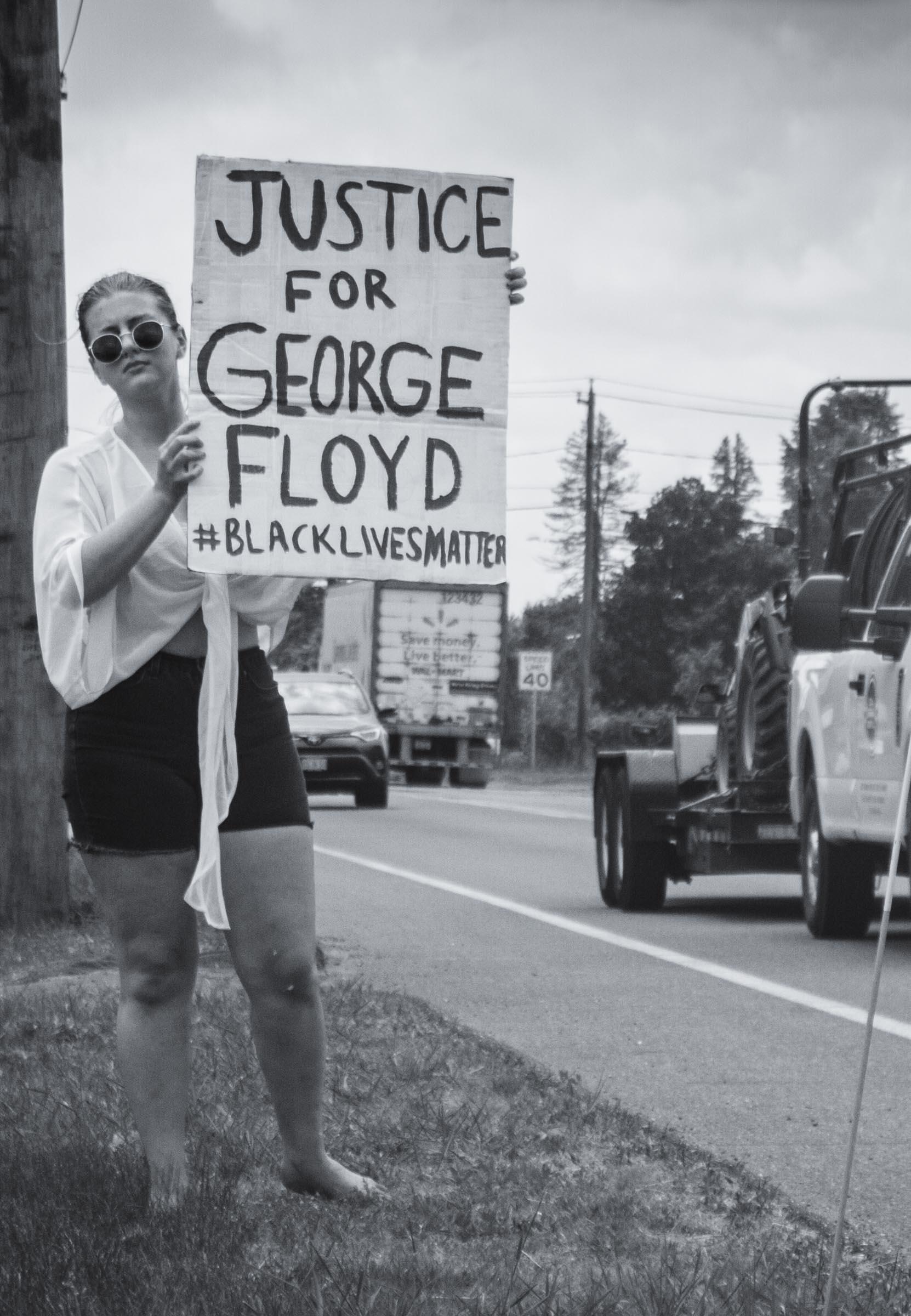 A solo protester holds up a 'Justice for George Floyd' placard along Route 9 in Hadley MA.